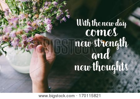 Life quote. Motivation quote on soft background. The hand touching purple flowers. With the new day comes new strength and new thoughts