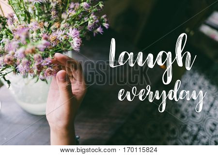 Life quote. Motivation quote on soft background. The hand touching purple flowers. Laugh everyday