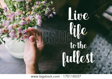 Life quote. Motivation quote on soft background. The hand touching purple flowers. Live life to the fullest.