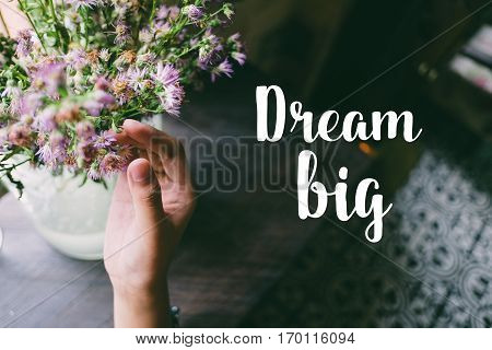 Life quote. Motivation quote on soft background. The hand touching purple flowers. Dream big.