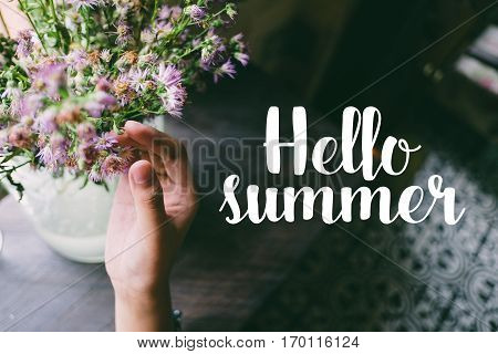 Life quote. Motivation quote on soft background. The hand touching purple flowers. Hello summer.
