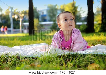 Funny little girl lying on the grass in summer park