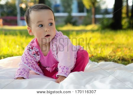 Funny little girl sitting on the grass in summer park