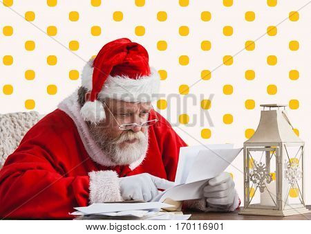 Santa claus reading christmas wish letter against yellow polka dot background