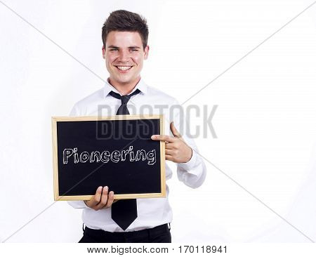 Pioneering - Young Smiling Businessman Holding Chalkboard With Text