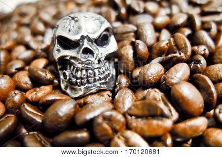 Metal skull in coffee beans dark roast