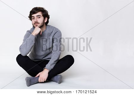 A portrait of young hipster with fair skin and trendy beard sitting on the floor crossed legs. Handsome man with nice face features relaxing on the floor. Isolated shot in studio over white background