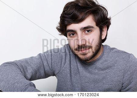 A close-up of young hipster with beard and moustache dark clever eyes isolated over white background having rest indoors looking thoughtful. Handsome bearded male model posing in studio