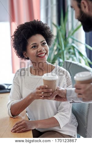 business, startup, people and drinks concept - happy african woman taking coffee cup from man in office