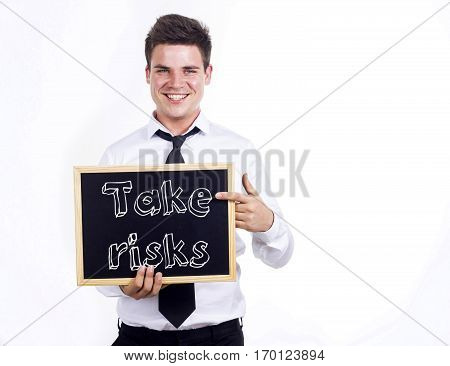 Take Risks - Young Smiling Businessman Holding Chalkboard With Text