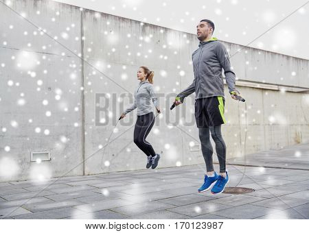 fitness, sport, people, exercising and healthy lifestyle concept - man and woman skipping with jump rope outdoors over snow