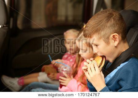 Cute children eating in a car