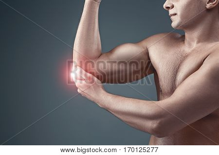 Man With Pain In Elbow. Pain relief concept on gray studio background