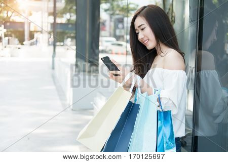 young asian woman using her smartphone and hold shopping bag while doing some shopping in a street shopping mall vintage tone and outdoor.