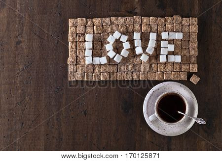 Word Love Made Of Brown And White Sugars And Cup Of Coffee