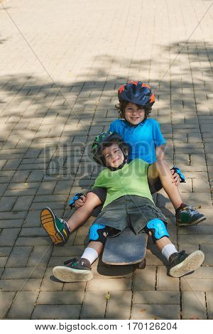 Funny little boy in protective helmet sitting on skateboard while his curly brother leaning back on him with wide smile