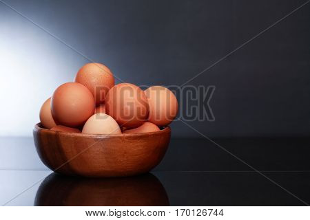 Heap of raw brown eggs in wooden bowl against dark background