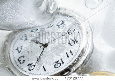 Closeup of pocket watch under frozen water background with ice