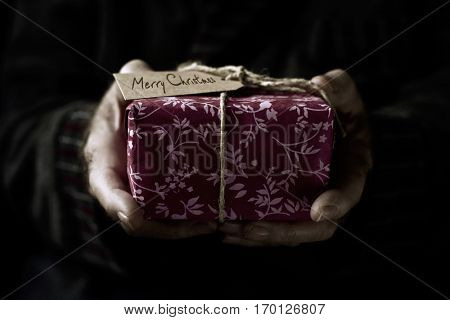 closeup of an old caucasian man holding a cozy gift tied with a jute string and a paper label with the text merry christmas written in it
