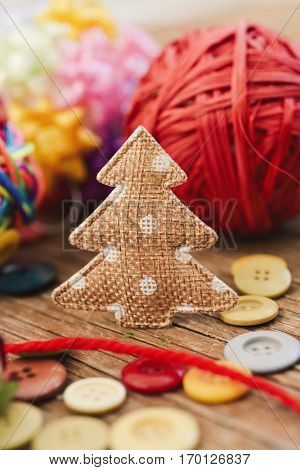 closeup of some cozy handmade christmas ornaments such as a fabric christmas tree and some christmas balls made with notions on a rustic wooden surface