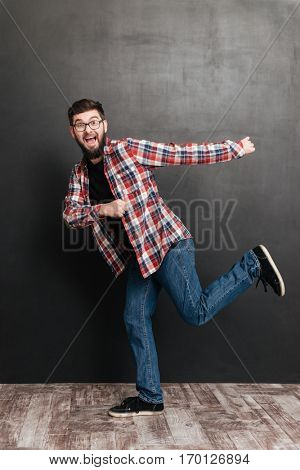 Cheerful bearded young man in glasses running and having fun over grey background