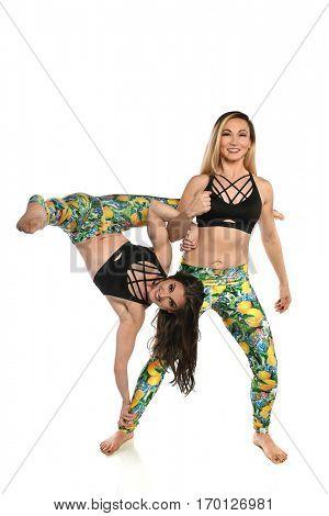 Women practicing balancing yoga isolated over white background