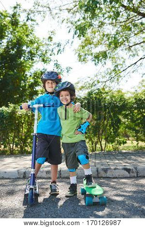 Portrait of curly little brothers in helmets and knee pads standing with one leg on kick scooter and skateboard