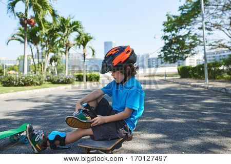 Full-length portrait of dark-haired little boy sitting on time-worn skateboard while putting on knee pads in lovely green park