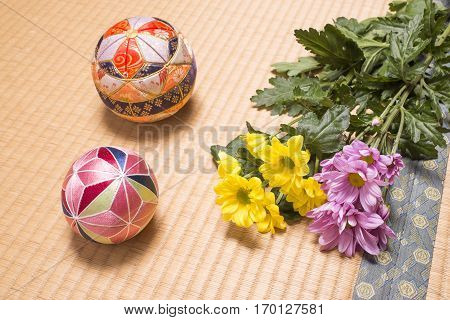 Traditional japanese handballs and chrysanthemum flowers on tatami mat