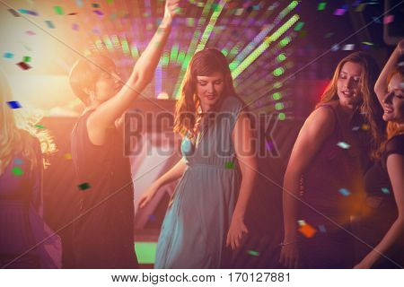 Group of smiling friends dancing on dance floor against flying colours