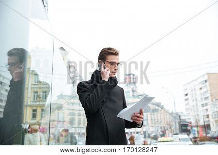 Side view of serious business man with phone and documents on the street