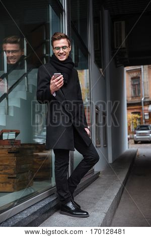 Vertical image of smiling business man in glasses with phone near the building. man looking at phone