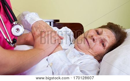 Picture of a sick elderly woman at home with her carer