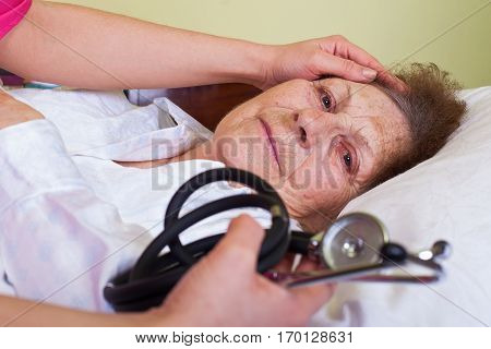 Picture of a bed ridden elderly woman with her care holding a stethoscope