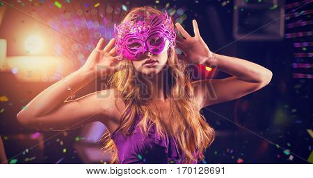 Woman with masquerade dancing on dance floor against flying colours
