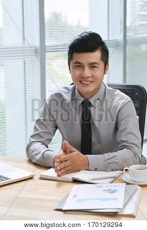Self-confident businessman distracted from making notes and looking at camera with toothy smile against panoramic windows