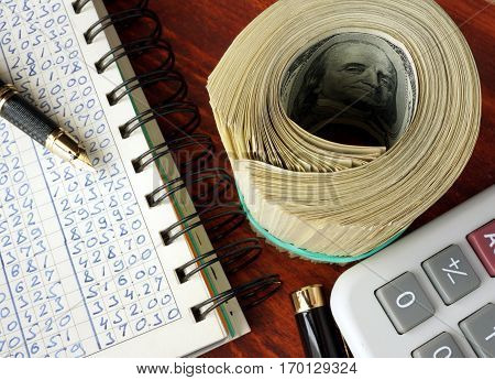 Ledger, pack of dollars and calculator. Accounting concept.