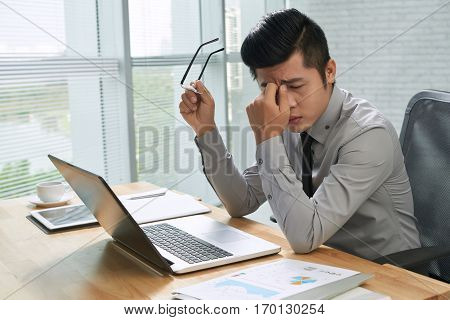 Tired young businessman taking off glasses and rubbing eyes while sitting at his workplace in office