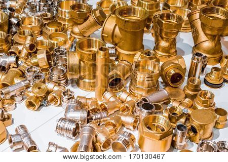 Scattering of various brass sanitary products. Tees, corners, connectors, nipples. Abstract industrial background