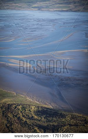 aerial view of the mudflat coastline at low tide with water winding in the mud and sand bank Frisian island Ameland The Netherlands