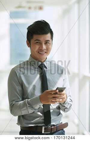 Cheerful Vietnamese businessman standing in office lobby while dialing number of his colleague on smartphone, waist-up portrait