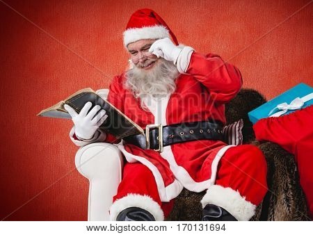 Santa claus sitting on chair and reading bible