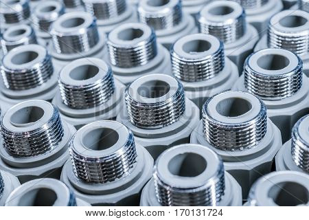 Polypropylene Plumbing connection fittings for plastic pipes. Orderly arranged in neat rows. Abstract industrial background.