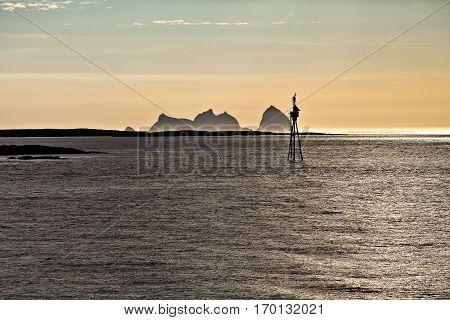 Midnight sun Norwegian Landscape with the mountain shape of Traena Island