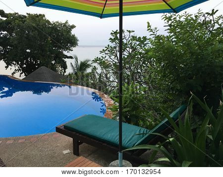 Outdoor swimming pool, sun bed and umbrella at the poolside and seaside.
