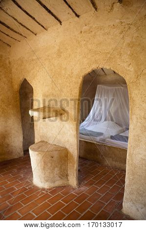Traditional adobe african hut interior with bed protected by mosquito net