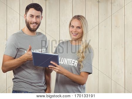 Portrait of volunteer couple using digital tablet and showing thumbs up against wooden background