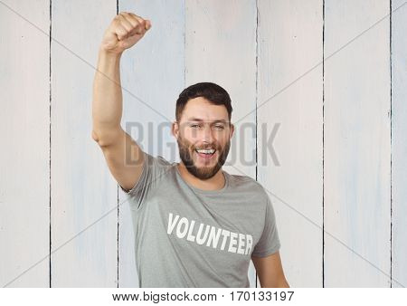 Volunteer raising fist to camera against wooden background
