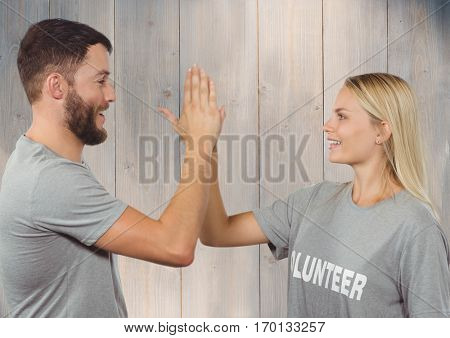 Volunteer couple in tshirt giving high five to each other against wooden background