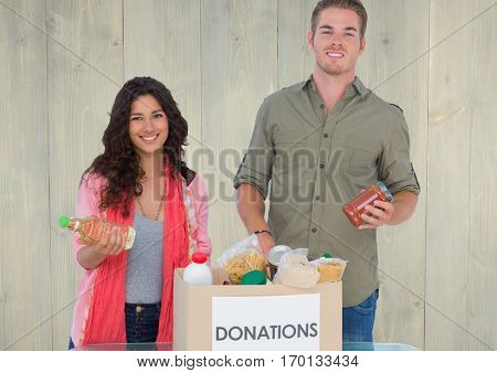 Portrait of smiling couple holding eatables from donations box against wooden background